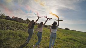 Happy friendly friends are running with toy planes that emit colored smoke. Happy friendly friends are running with toy planes that emit colored smoke stock video footage