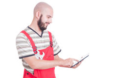 Happy and friendly mechanic using a wireless tablet Royalty Free Stock Photography