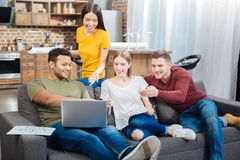 Happy friendly people sitting on the sofa and looking at the laptop. Incredible. Positive emotional friendly young people sitting on a soft sofa and smiling Royalty Free Stock Photos