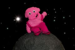 Happy friendly pink alien teddy. Fun cartoon style character on. Model moon in space scene. Funny extraterrestrial on the surface of a planet Royalty Free Stock Photography