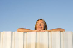 Happy friendly woman leaning relaxed over fence Stock Image