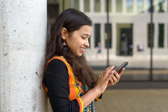 Happy friendly young Indian student. Happy attractive friendly young Indian student with long hair texting on her mobile phone as she leans against a wall Stock Photography