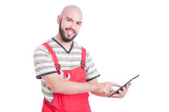 Happy friendly and young mechanic using a wireless tablet Royalty Free Stock Photo