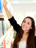Happy friendly young woman reaching for a book Royalty Free Stock Images