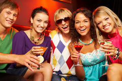 Happy friends. Portrait of young people with martini glasses laughing in the nightclub royalty free stock image