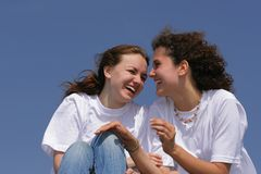 Happy friends. Two beautiful laughing girls against blue sky Royalty Free Stock Images