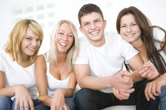 Happy friends. Group of young smiling friends sitting on a couch and looking at camera. Front view Royalty Free Stock Image