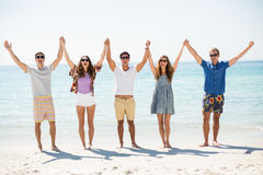 Happy friends with arms raised at beach Stock Photography
