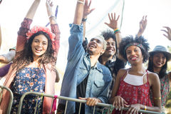 Happy friends with arms raised enjoying during music festival Royalty Free Stock Photos
