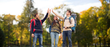 Happy friends with backpacks making high five. Travel, tourism, hike, gesture and people concept - group of smiling friends with backpacks making high five over Stock Photo