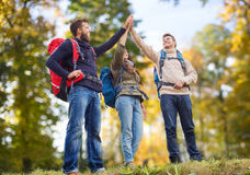 Happy friends with backpacks making high five Royalty Free Stock Photos