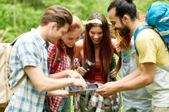 Happy friends with backpacks and tablet pc hiking royalty free stock photography