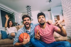 Happy friends or basketball fans watching basketball game on tv. And celebrating victory at home.Friendship, sports and entertainment concept royalty free stock photo