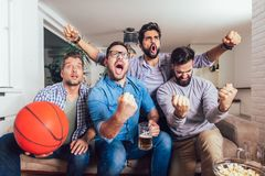 Happy friends or basketball fans watching basketball game on tv and celebrating victory at home. Friendship, sports and entertainment concept royalty free stock photography