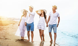 Happy friends on the beach. Happy friends strolling on the beach, outdoors Royalty Free Stock Photo