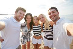 Happy friends on beach and taking selfie Stock Photography