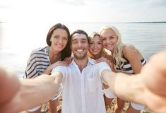 Happy friends on beach and taking selfie Stock Images