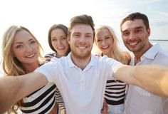 Happy friends on beach and taking selfie stock photos