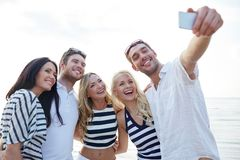 Happy friends on beach and taking selfie. Summer, sea, tourism, technology and people concept - group of smiling friends with smartphone on beach photographing stock photo