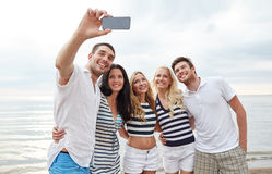 Happy friends on beach and taking selfie. Summer, sea, tourism, technology and people concept - group of smiling friends with smartphone on beach photographing stock photos