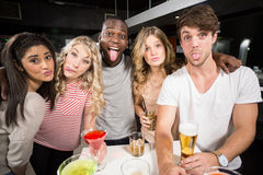 Happy friends with beer and cocktails sticking out tongue Royalty Free Stock Photos