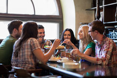 Happy friends with beer eating at bar or pub stock photos