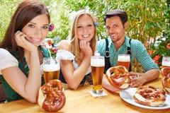 Happy friends in beer garden. Happy friends sitting in beer garden in Bavaria with pretzel royalty free stock image