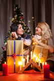Happy friends with big gift boxes in Christmas decorated room Stock Photography