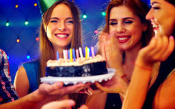 Happy friends birthday party with candle celebration cakes in club. Royalty Free Stock Photos