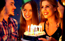 Happy friends birthday party with candle celebration cakes in club. Stock Photos