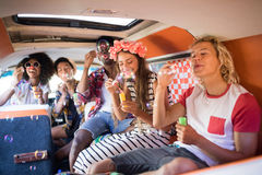 Happy friends blowing bubble wands in camper van Royalty Free Stock Photo