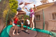 Happy friends bouncing on the outdoor trampoline royalty free stock photo