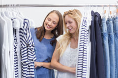 Happy friends browsing in the clothes rack Royalty Free Stock Photos