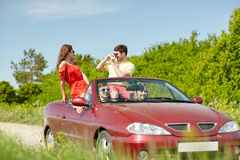 Happy friends with camera driving in cabriolet car Stock Photo
