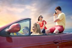 Happy friends with camera driving in car Stock Image