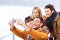 Happy friends with camera on skating rink Royalty Free Stock Photography