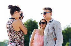 Happy friends with camera taking picture outdoors Royalty Free Stock Photo
