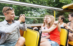 Happy friends with camera traveling by tour bus Stock Photo