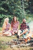 Happy friends at campfire. Bearded man and women smile at bonfire. Hipster in palid shirt and girls in vintage dresses. Happy friends at campfire. Bearded men royalty free stock images