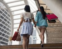 Happy friends carry shopping bags in city. Happy female friends look at each other during walking upstair. Two beautiful young Asian women shop in modern Bangkok Royalty Free Stock Image