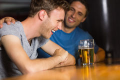 Happy friends catching up over pints Royalty Free Stock Images