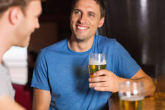 Happy friends catching up over pints Royalty Free Stock Photos