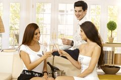 Happy friends celebrating with champagne. Happy young companionship celebrating with champagne at home, clinking glasses, smiling Stock Photo