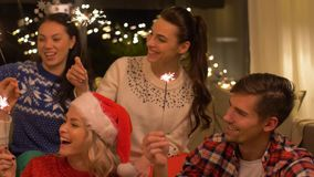 Happy friends celebrating christmas at home party. Celebration and holidays concept - happy friends with sparklers celebrating christmas at home party stock footage