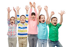 Happy friends celebrating victory. Childhood, fashion, gesture and people concept - happy smiling friends raising fists and celebrating victory Royalty Free Stock Images
