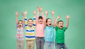 Happy friends celebrating victory. Childhood, preschool education, gesture and people concept - happy smiling friends raising fists and celebrating victory over Stock Image