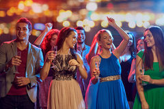 Happy friends with champagne dancing at nightclub Royalty Free Stock Image