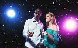 Happy friends with champagne flasses at night club party. Happy male and female multiethnic friends with champagne flutes at night club background with confetti Stock Images