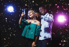 Happy friends with champagne flutes at night club party. Happy male and female multiethnic friends with champagne flutes at night club background with confetti Stock Image