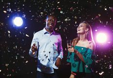 Happy friends with champagne flutes at night club party. Happy male and female multiethnic friends with champagne flutes at night club background with confetti Stock Photos